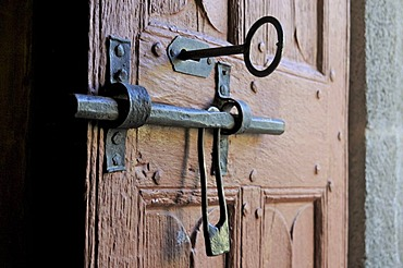 Old door of wood with its worn lock, Church in Cantal, Auvergne, France, Europe