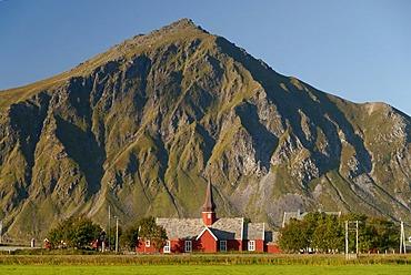 The red stave church of Flakstad in front of steep mountains, Vareid, Fredvang, island of Flakstadoya, Flakstadoya, Lofoten archipelago, Nordland, Norway, Europe