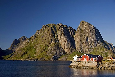 Typical red rorbuer huts, rorbu, at the coast of the Norwegian Sea, mountains at back, Hamnoy, island of Moskenesoy, Moskenesoy, Lofoten archipelago, Nordland, Norway, Europe