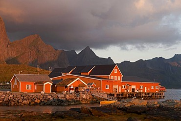 Rorbuer huts, rorbu, in warm morning light, in the tiny village of Sakrisoy, Sakrisoy, mountains behind, island of Moskenesoy, Moskenesoy, Lofoten archipelago, Reine, Nordland, Norway, Europe