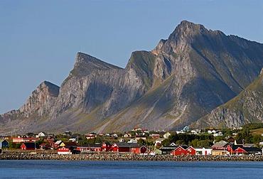 The red houses of Ramberg at the coast of the Norwegian Sea in front of the steep peaks of Flakstadoya, Flakstadoya island, Lofoten archipelago, Nordland, Norway, Europe