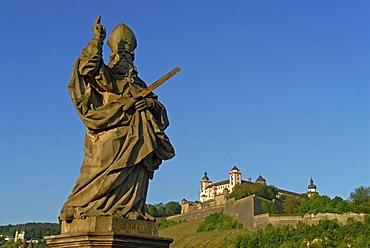 The statue of Saint Kilian on the Alte Mainbruecke, Old Main Bridge with the Festung Marienberg, Marienberg Fortress at back, Wuerzburg, Lower Franconia, Bavaria, Germany, Europe