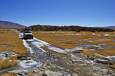 Off-road vehicle driving through an icy ford, Altiplano, Potosi, southern Bolivia, South America