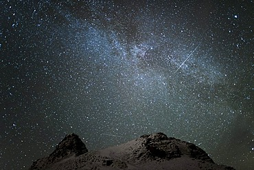 The Milky Way and two tracks of satellites on a starlit sky in winter, weak northern lights, aurora borealis on the lower sky, Longyearbyen, Spitsbergen, Svalbard, Norway, Europe