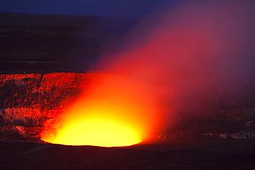 Magma in the Halema'uma'u Crater in the Kilauea Caldera illuminating the rising sulfur dioxide plume against the evening sky, Hawai'i Volcanoes National Park, Hawai'i, USA