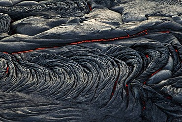 Molten pahoehoe type lava flowing from a crack in the East Rift Zone towards the sea, lava field of the Kilauea shield volcano, Hawai'i Volcanoes National Park, Kalapana, Hawai'i, USA