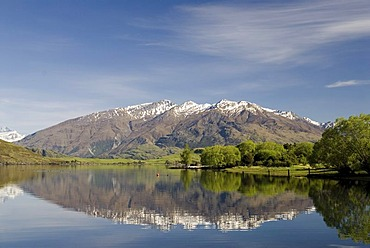 Mountains of the southern alps, reflected in the calm waters of Lake Wanaka, South Island, New Zealand