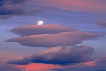 The rising moon behind colorful evening clouds near Lake Wanaka, South Island, New Zealand