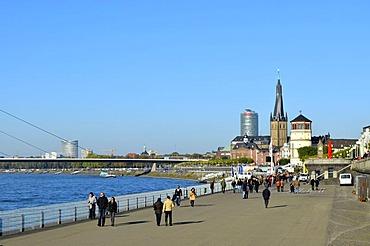Rheinuferpromenade, Rhine promenade, ramblers walking along the Rhine, historic town and Oberkasseler Bruecke bridge at back, Duesseldorf, Rhineland, North Rhine-Westphalia, Germany, Europe