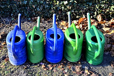 Several blue and green watering cans, cemetery, Borken, Muensterland, North Rhine-Westphalia, Germany, Europe