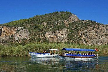 Excursion boats on the Dalyan river in front of the rock tombs of Caunos or Kaunos near Marmaris, Turkish Aegean Coast, Turkey