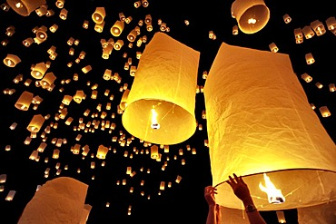 Traditional fire lanterns being released into the night sky during the Yeepeng festival, also referred to as Loi Krathong, in Chiang Mai, Thailand, Asia