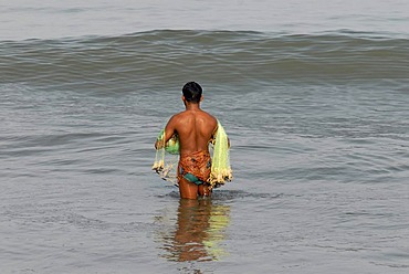 Fisherman with a net standing in the water, near Beypore, Kerala, Malabar Coast, southern India, Asia