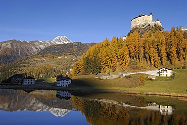 Schloss Tarasp Castle with Lake Tarasp in front of larch forest with autumnal colouring, Tarasp near Scoul, Lower Engadine, Grisons, Switzerland, Europe