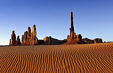 Sand dunes in front of Totem Pole and Yei Bi Chei rock formations after sunrise, Monument Valley, Navajo Tribal Park, Navajo Nation Reservation, Arizona, Utah, United States of America, USA