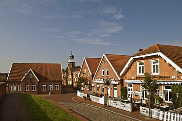 Row of houses and church on the dyke, Ditzum, East Frisia, Lower Saxony, Germany, Europe