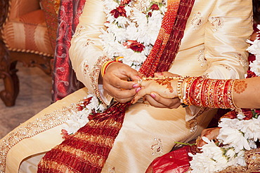 Indian groom passing wedding ring on his bride's finger