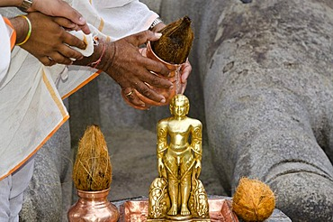 Two Jain pilgrims are pouring water over a small statue at the feet of the statue of Lord Gomateshwara, the tallest monolithic statue in the world, dedicated to Lord Bahubali, carved out of a single block of granite stone, 18 meters high, 983 AD, Sravanab