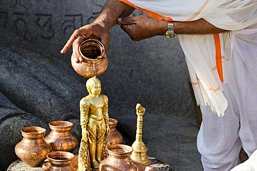 Jain pilgrim is pouring water on the small statue at the feet of the gigantic statue of Gomateshwara in Sravanabelagola, Karnataka, India, Asia