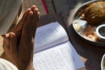 Jain pilgrim is reciting religious texts at the feet of the gigantic statue of Gomateshwara in Sravanabelagola, Karnataka, India, Asia