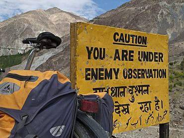 "Traveller's bicycle leaning against warning sign, ""Caution, you are under enemy observation"", in the area around Kargil, Jammu and Kashmir, India, Asia"