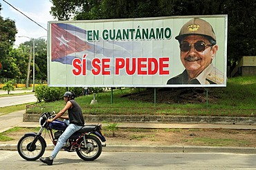 Motorcyclist in front of a sign with revolutionary propaganda, En Guantanamo si se puede, Guantanamo, Cuba, Caribbean