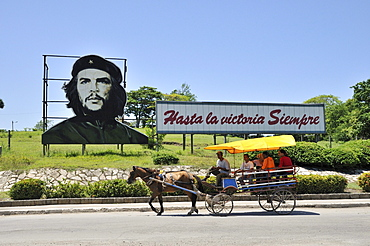 "Horse-drawn carriage in front of revolutionary propaganda, ""Hasta la victoria siempre"", Spanish for ""ever onward to victory"" with portrait of Ernesto ""Che"" Guevara, Las Tunas, Cuba, Caribbean"