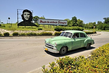 "Vintage car in front of revolutionary propaganda, ""Hasta la victoria siempre"", Spanish for ""ever onward to victory"" with portrait of Ernesto ""Che"" Guevara, Las Tunas, Cuba, Caribbean"
