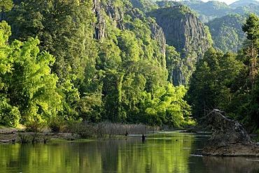 Subtropical river landscape with Lao fishermen fishing with simple nets, Tham Kong Lor, amidst the dense subtropical rainforest, Khammouane, Laos, Southeast Asia, Asia