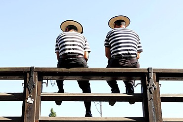 Two gondoliers sitting on a railing, from behind, Venice, Italy, Europe