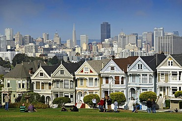 Tourists in front of Painted Ladies, Victorian, multi-coloured painted wooden houses in front of the skyline with the Transamerica Pyramid, Steiner Street, Alamo Square, San Francisco, California, United States of America, USA, PublicGround