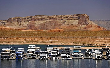 House boats are moored in the harbour of Antelope Point Marina with Tower Butte at back, Lake Powell, Wahweap Marina, Glen Canyon National Recreation Area, Page, Arizona, United States, USA