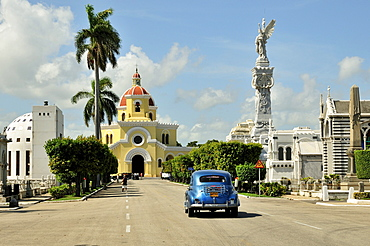 Classic car driving in front of a chapel on Colon Cemetery, Cementerio Cristobal Colon, named after Christopher Columbus, Havana, Cuba, Caribbean