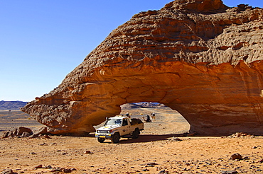 Off-road vehicle driving though a rock arch shaped by wind erosion, Acacus Mountains, Sahara desert, Libya, Africa