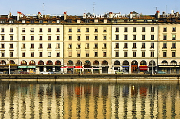 A row of houses on Quai des Bergues street is being reflected in the water of the Rhone River in downtown Geneva, Switzerland, Europe