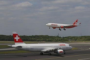 Passenger airplane of Swiss International Air Lines Ltd. on the runway, behind an airberlin airplane departing, Duesseldorf International Airport, Duesseldorf, North Rhine-Westphalia, Germany, Europe