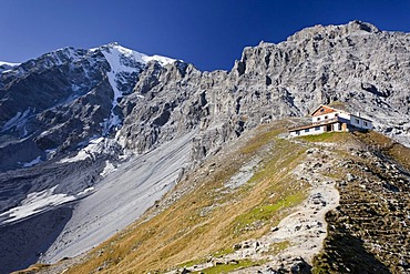 View of the Tabarettahuette mountain lodge, north face of Ortler mountain at the back, during the ascent to the Tabaretta fixed rope route, region of Ortler mountain, province of Bolzano-Bozen, Italy, Europe