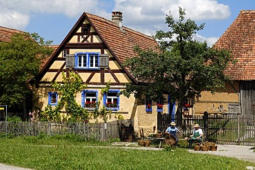 Haeckerhaus building, 1706, left, left, on the right a barn, 1590, both from Ergersheim, in front two basket weavers, Franconian open-air museum, Eisweiherweg 1, Bad Windsheim, Middle Franconia, Bavaria, Germany, Europe