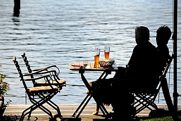 Snack beside the lake, silhouettes of two people sitting at a table, Lake Ratzeburg, Ratzeburg, Schleswig-Holstein, Germany, Europe