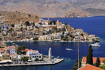 Overlooking the picturesque houses and the clock tower of the small island of Symi near Rhodes, Greece, Europe