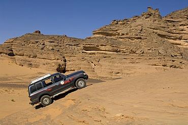 SUV climbing rock, Akakus, Acacus Mountains or Tadrart Acacus, Sahara desert, Fezzan, Libya, North Africa