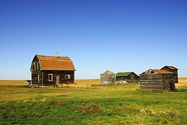 Old abandoned house with barn and grain silos in the Prairies, Saskatchewan, Canada