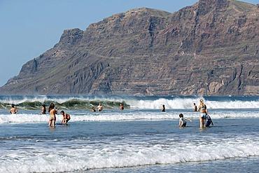 Tourists in the water, beach Playa de Famara, La Caleta de Famara, west coast of Lanzarote, Canary Islands, Spain, Europe