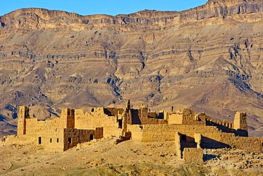 Ruined Kasbah on a hill, a former Berbers' house built of adobe, mountain range of the Djebel Kissane table mountain at the back, Draa Valley, southern Morocco, Morocco, Africa