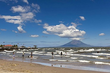 People walking on the shallow shore of Lago de Nicaragua with the volcanic island of Ometepe and the stratovolcano Volcan Concepcion at back, San Jorge, Nicaragua, Central America