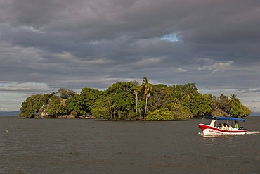 Tourist boat in front of small island with tropical vegetation in Lake Nicaragua, Isletas, Lago de Nicaragua, Nicaragua, Central America