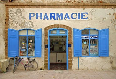 The facade of a pharmacy with a blue door frame and blue window shutters in Essaouira, Morocco, Africa