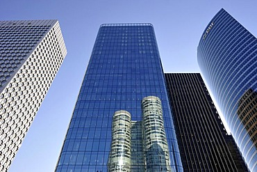 Skyscrapers, Tour Coeur Defense reflected in the glass facade of the Opus 12 building, between the Tour Initiale, left, and Tour EDF towers, right, La Defense, Paris, France, Europe