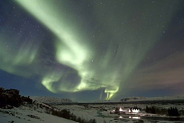 Northern Lights (Aurora borealis) above the plane and the historic buildings of fiingvellir, Iceland, Europe