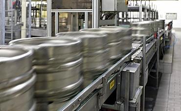 Beer kegs on a conveyor belt, waiting to be filled, with motion blur, Binding brewery, Frankfurt, Hesse, Germany, Europe
